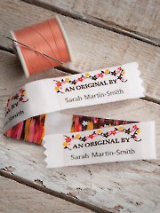 """This beautifully woven design is perfect for adding a special little something extra to your next craft project. Each label is precut with pinked edging, is washable, and has a woven heading and design with the personalized part printed in red. Each label is 2 1/4"""" x 7/8"""".Important: Please type desired name (you have up to 18 letter/spaces) in the Required Information field of the shopping cart when completing your Internet order. Drop shipped from our supplier. Please allow 3-4 weeks for delivery. Shipments available to the 48 contiguous states only."""